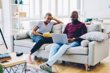 Young african american family spending time at home interior resting with reading book and using laptop computer,hipster guy watching video on netbook sitting next to his girlfriend enjoy novel