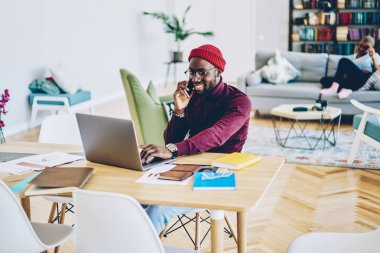 Happy dark skinned male satisfied with mobile phone conversation with customer support installing app on laptop computer,smiling african american man freelancer satisfied with online busines