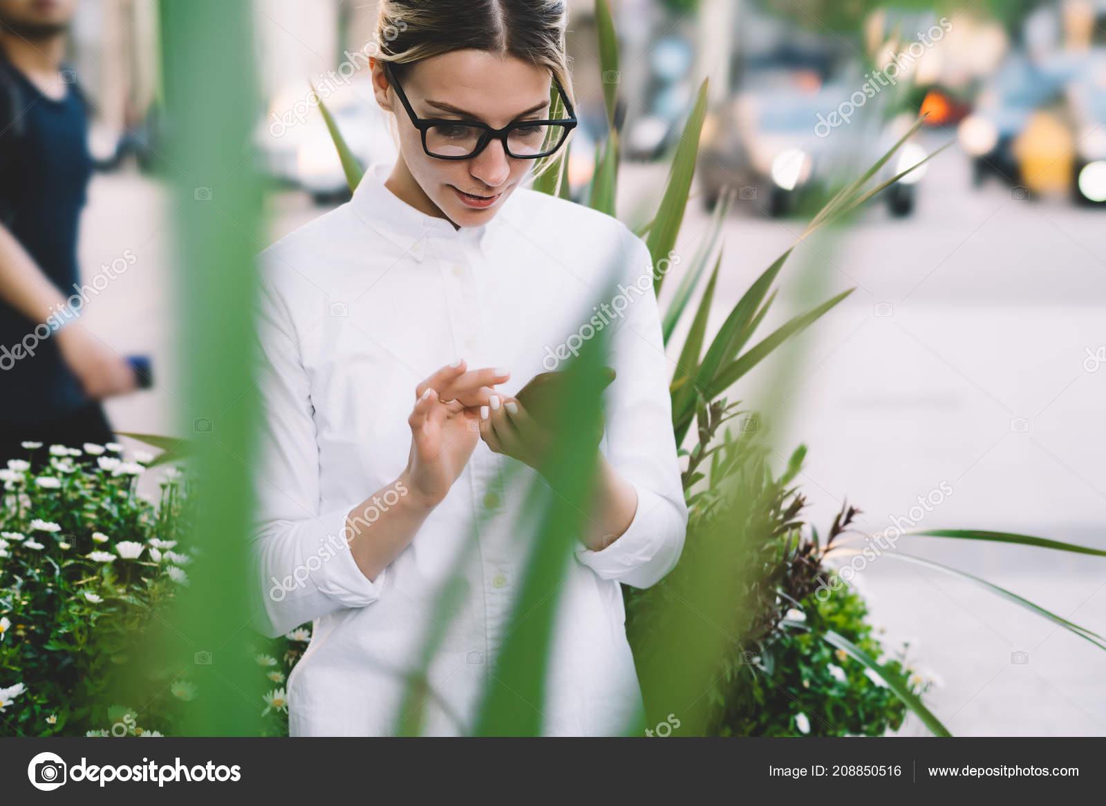 055f5e27c4ac Mladá žena na sobě oblečení čtení novinek na webových stránkách na moderní  smartphone zařízení pomocí připojení k Internetu 4g. Bokovky dívka v  brýlích drží ...