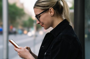 Side view of positive hipster girl laughing while chatting with followers in blog on smartphone.Cheerful young woman in eyeglasses watching video on website on digital mobile phone using 4G internet