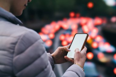 Cropped view of young woman messaging in online chat on blank display of modern smartphone using 4G internet connection on blurred background with night lights.Female hands holding mobile phone device stock vector
