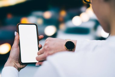 Cropped back view of woman's hand holding smartphone with blank screen for your internet website and checking time on watch on another hand on bokeh background.Digital telephone with copy space area