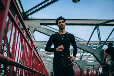 Strength male athlete running on city bridge during enjoying music on radio via electronic headphones using smartphone media application, young sportsman training body during jogging outdoors