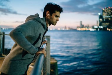 Male runner resting on railing near river after jogging across night city during listening audio guidelines about evening flexibility exercises, serious sportsman pondering on healthy lifestyle