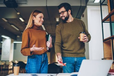 Two business coworkers 20 years old communicated positively in comfortable office during coffee break, handsome hipster guy in spectacles holding drink while attractive girl staying with books indoors
