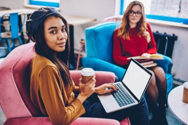 Portrait of hipster girl holding takeaway coffee and laptop computer with mock up area for your internet advertising sitting with friend on blurred background, concept of technology and communication