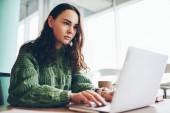 Zamyšlený kavkazské tisícileté dívka učí během on-line kurzy na přenosném počítači během volného času, ženské blogger psaní publikace pro sdílení na sociálních sítích pomocí bezdrátové připojení a netbook