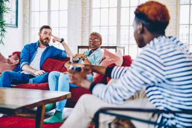 Group of male and female friends spending free time together at modern designed living room in apartment communicating with each other, multiracial hipsters having conversation at home interior