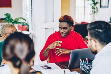 Dark skinned male team member gesturing while explaining information to crew of coworkers sitting at desktop with laptop computer, clever hipster guy communicating with multiracial group of colleagues