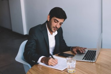 Young indian businessman writing plan in textbook enjoying paper work sitting at desktop with laptop device and glass of water, handsome employer spending time for searching information on netbook
