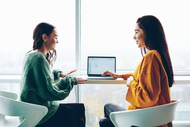 Positive caucasian women talking to each other sitting at loft interior office with laptop computer discussing information from networks, smiling female colleagues communicating about work project
