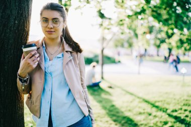 Young caucasian girl in spectacles holding coffee to go cup looking at camera resting in park listening music, half length portrait of female hipster enjoying playlist in earphones on spring day