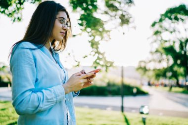 Thoughtful brunette woman in spectacles looking away listening audio book while spending time in park on leisure, hipster girl enjoying music from playlist using cellular and modern earphones