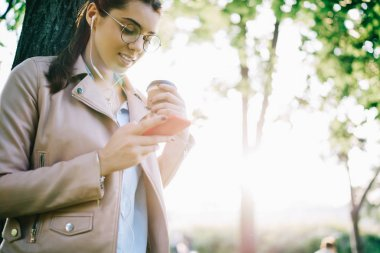 Attractive hipster girl in eyewear checking notification on smartphone download new song to playlist, female meloman listening to music in earphones via app while having coffee break outdoors
