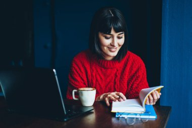 Cheerful hipster girl reading literature for education spending time at cafeteria for autodidact, smiling woman with bob haircut enjoying positive book and cappuccino sitting at desktop with laptop