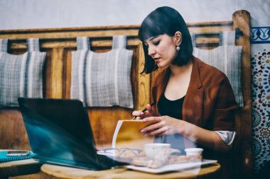 Clever intelligence female writer searching information for creating new best seller using modern laptop device and literature during free time at cafeteria, concept of education and knowledge