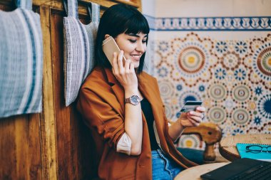 Cheerful hipster girl checking banking balance while calling to consultancy center holding credit card in hand and dictate number for transaction, smiling woman confirm purchase via phone conversation
