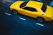 Top view of yellow powerful sport car with chromes wheels parked on asphalt road in town, bright vehicle automobile with copy space area for service name or logo waiting for order on city stree