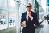 Fényképek Magabiztos elegáns formai öltözött vállalkozó rögzítésével nyakkendő, miközben nézi a kamera portréja. Fiatal üzletember smartphone és kávéval a kezében áll a modern épület elegáns öltöny