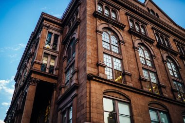 Historic building with big vintage windows on exterior with apartments for residents in district of megalopolis,angle view of beautiful old architecture facade with real estate for rent inside