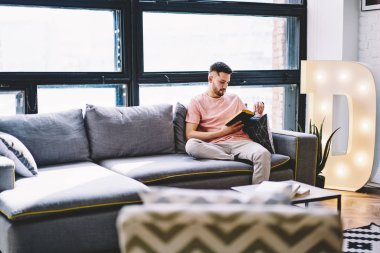 Pensive young man resting at home on comfortable sofa and reading book in modern apartment with stylish interior.Hipster guy enjoying literature plot sitting on cozy couch in design flat