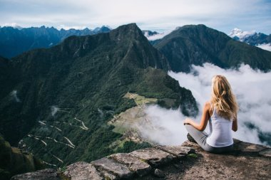 Young woman tourist sitting in lotus relaxing and admiring breathtaking view during trek.Experienced female traveler enjoying beauty of green landscapes and high mountains covered clouds