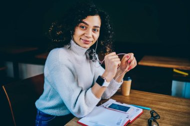 Young carefree hipster girl looking at camera enjoying romantic audio book sitting at wooden table and waiting colleague for informal meeting, smiling female meloman listening playlist indoors