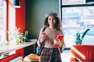 Half length portrait of cheerful hipster girl standing at cozy cafeteria with loft interior holding textbook enjoying audio with high volume via headphones while communicated with friends on cellphone