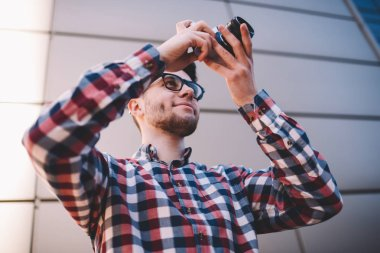 Professional male photographer in trendy shirt satisfied with work making images on modern equipment, young hipster guy fond of photography enjoying leisure with taking pictures on vintage camera