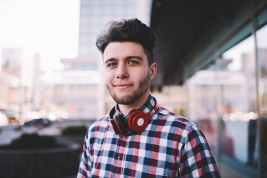 Portrait of handsoem young man in casual wear and with modern acessory for listening music looking at camera standing on street, hipster guy with red stereo headphones enjoying leisure outdoors