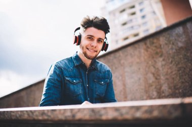 Half length portrait of happy millennial male in headphones spending time on street, handsome positive young hipster guy entertaining with favourite playlist in stereo accessory standing outdoors