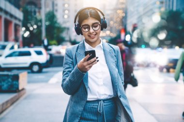 Cheerful and carefree young woman enjoying recreation time in city with favourite music in headphones. Attractive smiling female singing song and listening playlist on smartphone.Browsing LTE internet