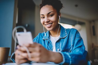 Portrait of cheerful dark skinned female teenager smiling at camera while listening favourite songs in electronic headphones, positive hipster girl enjoying music on radio station using mobile app