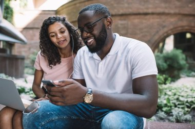 African American couple in love chatting with followers from website via smartphone and laptop applications, positive couple in love choosing music for listening on leisure sitting on urban setting