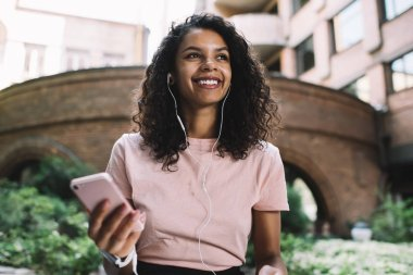 Happy woman in electronic headphones looking away and smiling while listening positive audio book connected to 4g internet on cell smartphone for using knowledge application, millennial people