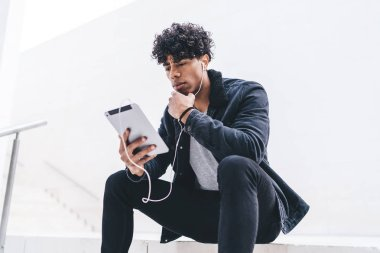 Male blogger listening music player online on website in earphones connected to digital tablet sitting outdoors, pensive man watching video in networks on touch pad using public wireless internet