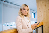 Fotografie Successful female office worker in elegant wear looking at camera during break from chatting online with colleagues via mobile application, attractive businesswoman with blonde hair holding cellular