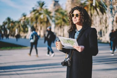 Attractive caucasian hipster girl dressed in stylish apparel holding paper map and takeaway coffee and looking away during sightseeing in city, teenage woman enjoying time for travelling to town