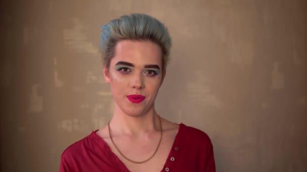 glücklich lächelnder schwuler Mann mit Make-up Travestie-Diva Transvestit blaues Haar aus nächster Nähe