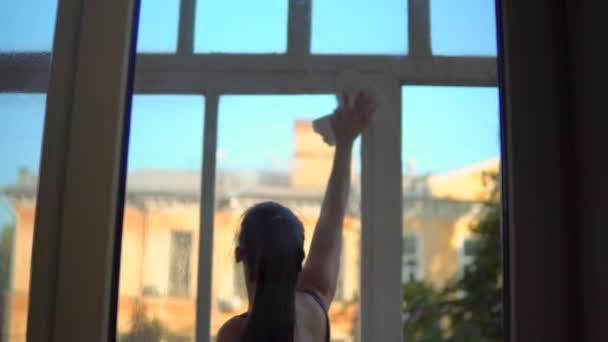 Ženské čištění oken pomocí rozstřikované kapaliny čištění pro setření skla, uklidit