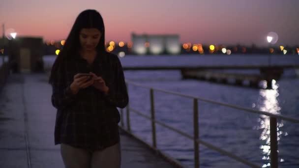 Atraktivní žena pomocí mobilu na nábřeží, procházky po ulici a textování telefonem