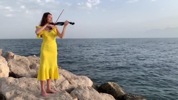 Fiatal gyönyörű zenész lány sárga ruhában játszik elektromos hegedű sziklák közelében Földközi-tenger. Szabadtéri szóló koncert koncepció. 4k stock videó.