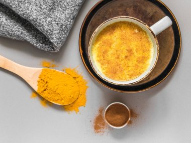 Turmeric latte with milk and cinnamon. Elixir of health and vivacity. Traditional healthy Indian detox drink. Grey background, top view
