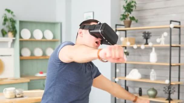 aufgeregter junger Mann mit Virtual-Reality-Headset tanzt und spielt 360-Grad-Videospiel zu Hause