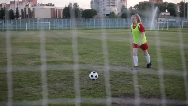 Školní fotbalový hráč kopající míč na branku