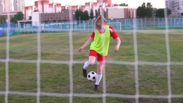 Dívčí fotbalový hráč v pomalém pohybu s fotbalovým míčkem