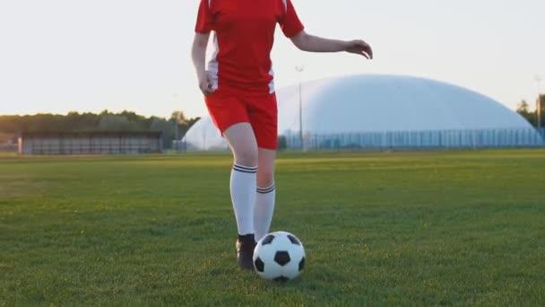 Fußballerinnen in roter Uniform kicken bei Sonnenuntergang in Zeitlupe