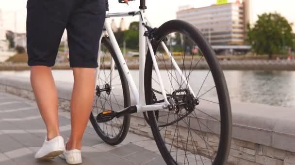 Zavřete mužské nohy, které jdou s silničním motorku na ulici. Zpomaleně