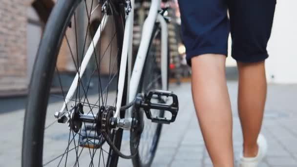 Poblíž příležitostného bicyklu, který řídil bílé silniční kolo ve městě. Zpomaleně