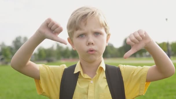 Emotional portrait of blond unhappy boy giving thumbs down hand gesture. Angry child looking with disapproval facial expression